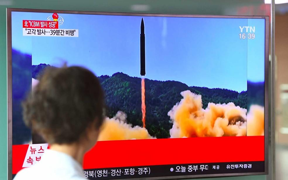 Uma mulher observa uma TV de uma estação ferroviária de Seul, na Coreia do Sul, que mostra imagem de um lançamento de míssil balístico da Coreia do Norte (Foto: Jung Yeon-Je / AFP Photo)
