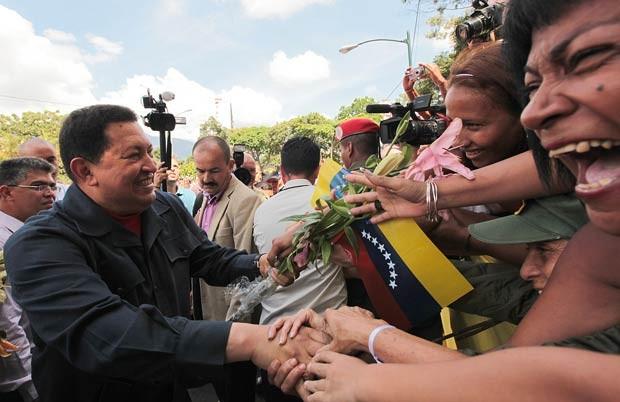O presidente da Venezuela, Hugo Chávez, é cercado após votar neste domingo (7) (Foto: AFP)