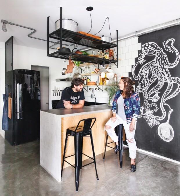 Felipe e Gabriela aproveitam o ambiente, junto da bancada de concreto produzida por Onofre, com banquetas da Tok & Stok. Chapa metálica perfurada foi empregada no paneleiro preso ao teto, projetado pelo Metamoorfose Studio (Foto: Maíra Acayaba / Editora Globo)