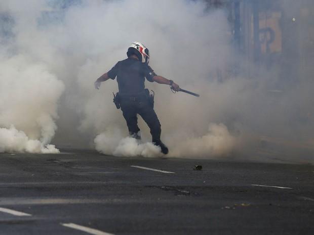 1º/6 - Policial chuta uma bomba de gás lacrimogêneo na direção de manifestantes durante confronto após protesto contra o governo interino de Michel Temer na Avenida Paulista, em São Paulo (Foto: Miguel Schincariol/AFP)