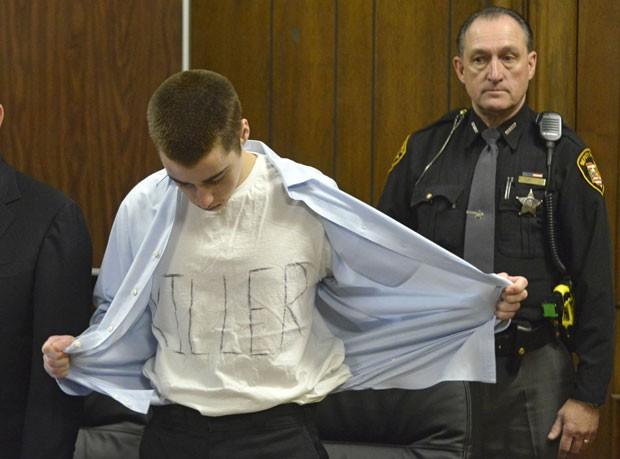 T. J. Lane desabotoa a camisa e exibe a palavra 'assassino' escrita em sua camiseta (Foto: Reuters/Duncan Scott/The News-Herald)