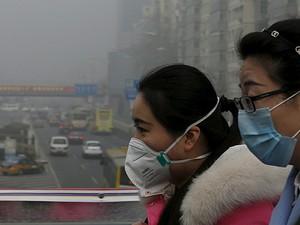 Mulheres usam máscaras para se proteger de poluição em Pequim, na China