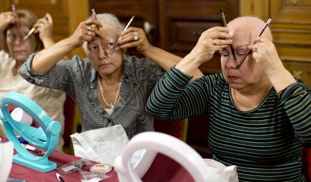 Pacientes que realizam tratamento contra o câncer participam de aula e tentam determinar o tamanho de suas sobrancelhas (Foto: Natacha Pisarenko/AP)