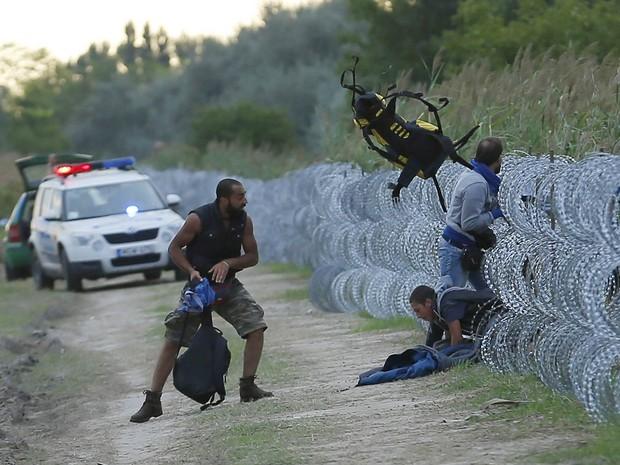 Migrantes sírios passam por barreira de arame farpado tentando adentrar o território húngaro na fronteira Sérvia-Hungria, enquanto policiais húngaros observam ao fundo, perto de Roszke, Hungria. O país iniciou a construção de uma cerca de 175 km na região (Foto: Laszlo Balogh/Reuters)