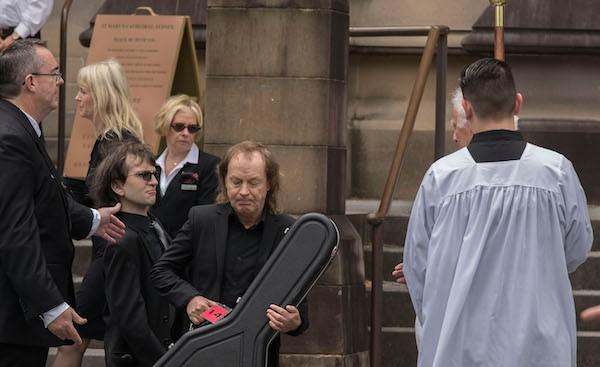 O músico Angus Young com o sobrinho Ross, filho de Malcom Young, carregando a guitarra do irmão, músico do AC/DC, em seu funderal (Foto: Getty Images)
