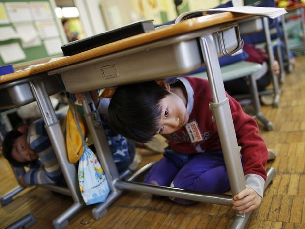 Aluno de escola de Tóquio se protege debaixo de carteira durante simulação de terremoto (Foto: Issei Kato/Reuters)