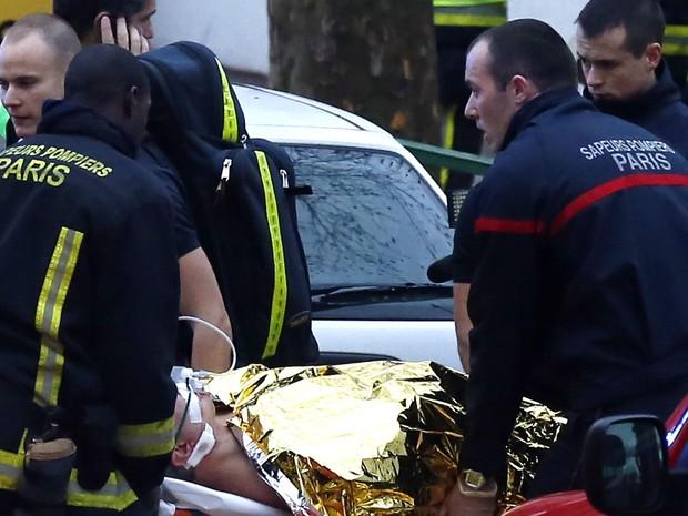 Ferido é resgatado em Montrouge, no Sul da França, após tiroteio nesta quinta-feira (8), um dia depois do atentado que matou 12 pessoas em Paris (Foto: Thomas Sanson/AFP)