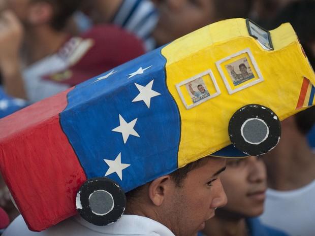 Apoiador de Capriles, o candidato da oposição na eleição à presidência da Venezuela, usa um chapéu com ministura de ônibus com as cores do país. (Foto: Raul Arboleda/AFP)