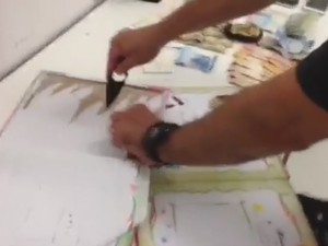 Policial corta capa de álbum onde droga estava escondida; no flagrante, paraguaia foi presa suspeita de tráfico (Foto: Polícia Federal/ Divulgação)