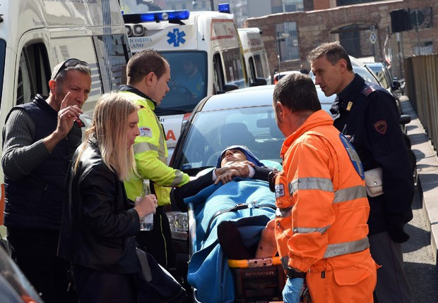 Ferido é retirado de tribunal em Milão, na Itália, após tiroteio que deixou dois mortos nesta quinta-feira (9) (Foto: AP Photo/Daniel Dal Zennaro, ANSA)