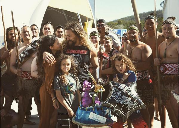 O ator Jason Momoa, com esposa, filhos e amigos e com o bolo do Aquaman (Foto: Instagram)