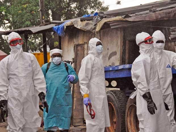 Agentes de saúde da Libéria chegam à casa de um homem que morreu contaminado pelo vírus. (Foto: Abbas Dulleh / AP Photo)