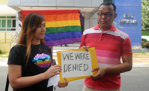 Maria Arlyn Ibanez e pastor Crescencio Agbayani seguram placa em protesto fora do cartório de registro civil de Manila (Foto: Jay Directo / AFP)
