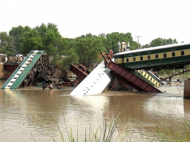 Um trem que transportava soldados paquistaneses é resgatado após queda de uma ponte por onde passava em um canal em Wazirabad, perto de Lahore, no Paquistão. Pelo menos 12 soldados morreram no acidente (Foto: Rameez Khan/AP)