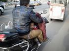 Chinês anda com scooter carregada e leva criança espremida nas pernas