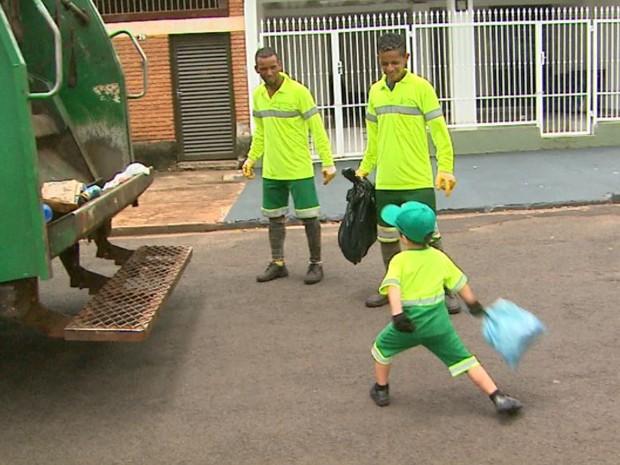 Miguel arremessa o lixo de casa para dentro do caminhão da limpeza em Ribeirão Preto, SP (Foto: Ronaldo Gomes/EPTV)