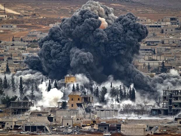 Densa nuvem de fumaça escura sobe ao céu após ataque aéreo da coalizão comandada pelos EUA na cidade de Kobani, na Síria, em combate ao grupo terrorista Estado Islâmico (EI). A foto foi feita de um morro perto de Suruc, na Turquia, perto da fronteira (Foto: Vadim Ghirda/AP)
