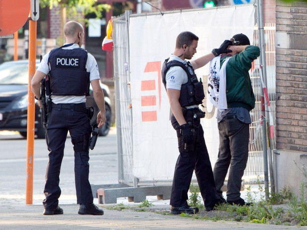 Policiais checam a identidade de um homem perto da sede do Departamento de Polícia em Charleroi, na Bélgica, no sábado (6) (Foto: AP Photo/Virginia Mayo)