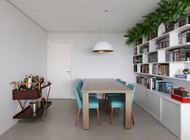 Além da estante, a mesa de jantar também é personalizada para o casal, projetada e executada pelo escritório GF Projetos. Cadeiras da Oppa. Pendente da Decorlight.  Barzinho da Clami  (Foto: Mariana Orsi/Divulgação)