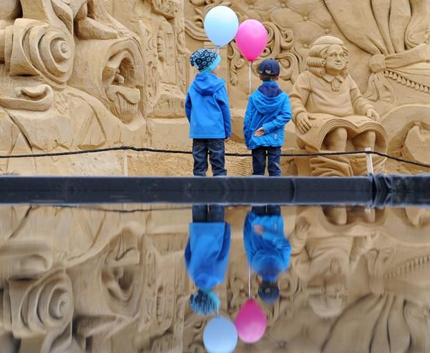 Meninos observam escultura 'Boas Notícias', feita em areia pelos artistas Mikhail Fedotov e Zamir Yushaev (Foto: Daniel Bockwoldt/AFP)