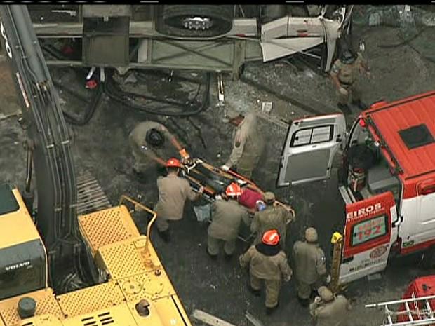 Outra vítima é levada para ambulância, após queda de ônibus (Foto: Reprodução / TV Globo)