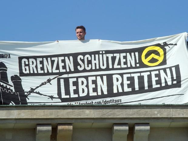 Faixa com a mensagem 'Proteja as fronteiras, salve vidas!' é exibida por manifestantes de um grupo da ultradireita em Berlim, na Alemanha, durante protesto contra imigrantes (Foto: Paul Zinken/dpa/AFP)