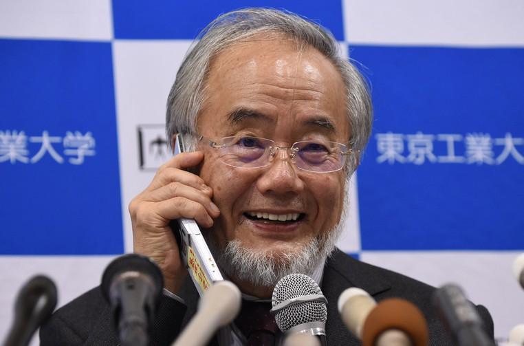 Yoshinori Ohsumi sorri ao falar pelo telefone com o primeiro-ministro Shinzo Abe durante coletiva de imprensa em Tóquio, no Japão, após anúncio de que que ele havia sido laureado com o Prêmio Nobel (Foto: Toru Yamanaka/AFP)