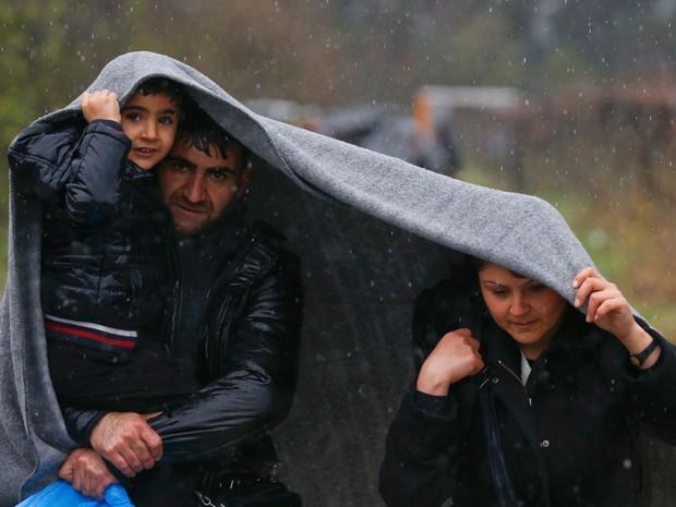 Migrantes se protegem da chuva com um cobertor durante caminhada para atravessar a fronteira da Grécia com a Macedônia (Foto: Stoyan Nenov/ Reuters)