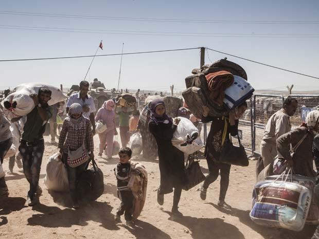 Refugiados curdos da Síria passam atravessam a fronteira com a Turquia, perto da cidade de Kobani (Foto: UNHCR / I. Prickett)