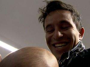 Pai sorri com o bebê no colo na chegada a Belo Horizonte (Foto: Reprodução/TV Globo)