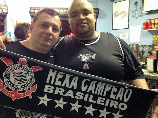 Rogério (à direita) posa com um amigo e a faixa de hexacampeão (Foto: Glauco Araújo/G1)