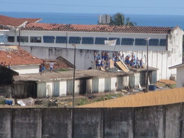 Presos voltaram a ocupar os telhados dos pavilhões co paus, pedras e bandeiras com siglas de facções criminosas (Foto: Andrea Tavares/G1)
