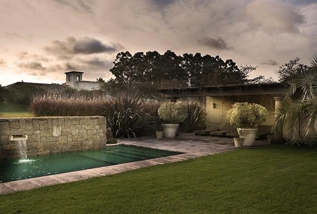 A piscina amparada por uma parede de pedra, na área externa da casa (Foto: Marcio Scavone)