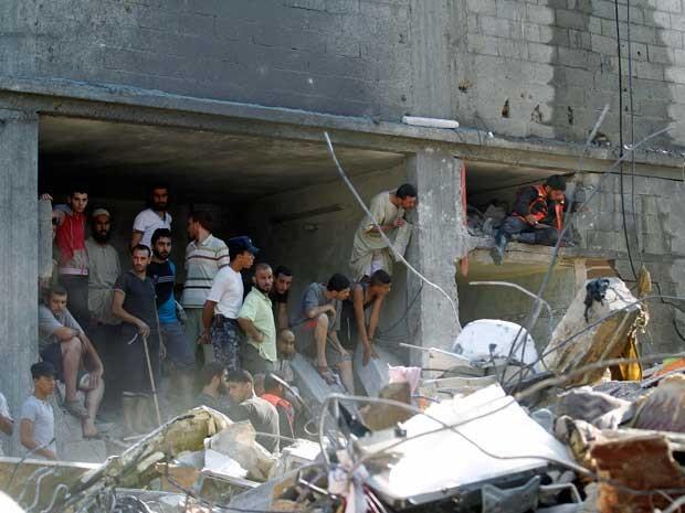 Palestinos se reúnem em escombros de um prédio destruído na sequência de um ataque militar israelense em Rafah, no sul da Faixa de Gaza. (Foto: Said Khatib / AFP Photo)