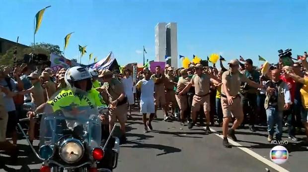 Manifestantescontra e a favor do impeachment se aproximam de condutores da tocha olímpica em Brasília (Foto: TV Globo/Reprodução)