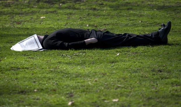Com jornal como máscara, homem tira soneca em parque. (Foto: Carl Court/AFP)