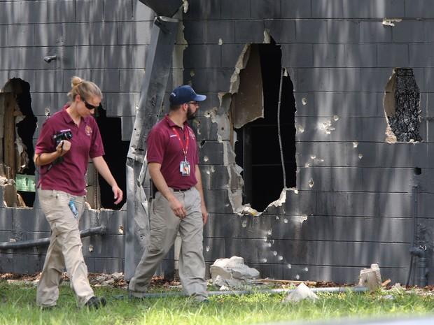 Investigadores do escritório do legista analisam o lado oeste da boate Pulse, onde um atirador abriu fogo neste domingo (12), em Orlando (Foto: Doug Clifford/The Tampa Bay Times via AP)