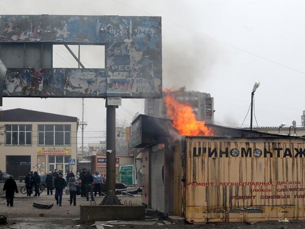 Moradores observam incêndio na cidade portuária de Mariupol, na Ucrânia, depois de bombardeio promovido por rebeldes (Foto: Stringer/AFP)