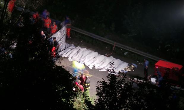 Corpos das vítimas são vistos alinhados após ônibus despencar de barranco de 30 m de altura na Itália (Foto: Agenzia Controluce,Stinger/AFP)