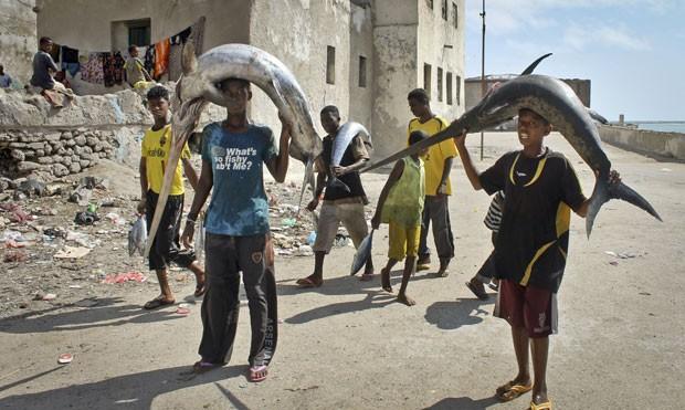 Pescadores levam peixes-espadas sobre a cabeça. (Foto: Farah Abdi Warsameh/AP)