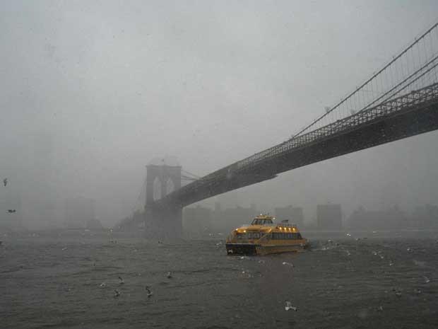Barco enfrenta o vento forte sob a ponte de Brooklyn, em Nova York. (Foto: Keith Bedford / Reuters)
