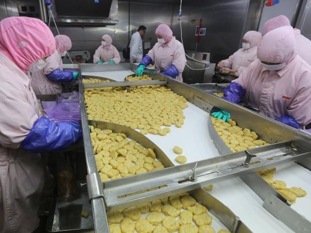 Foto feita neste domindgo (20) mostra produção de trabalhadores na Shanghai Husi Food Co, fábrica do OSI Group, em Xangai (Foto: AFP)