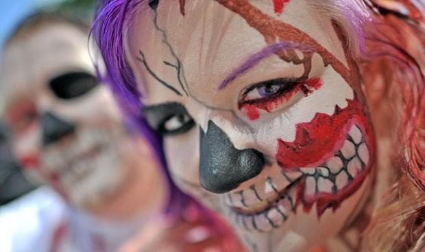 Participantes maquiados curtem o festival, que conta com música e artes (Foto: Hendrik Schmidt/AFP)