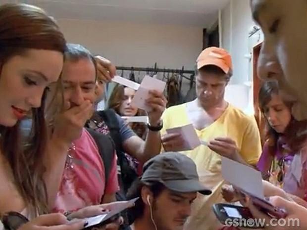 Os doze concorrentes abrem os envelopes que determinarão a sua vida (Foto: Atormentados/ TV Globo)