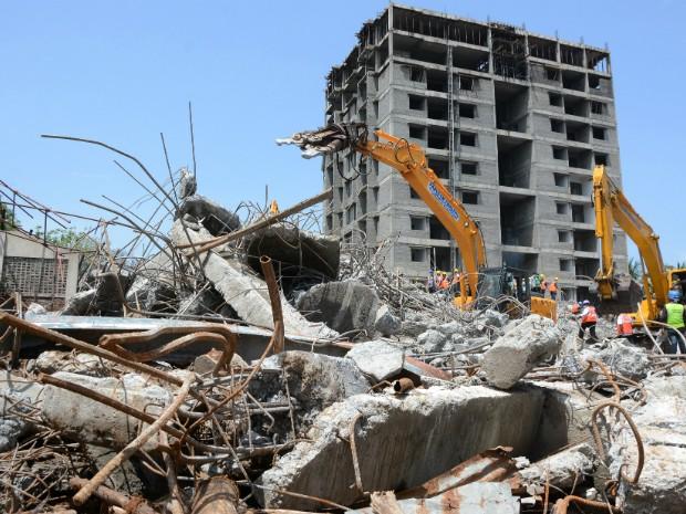 Equipes de resgate buscam vítimas entre os escombros do prédio na Índia (Foto: STRDEL/AFP)