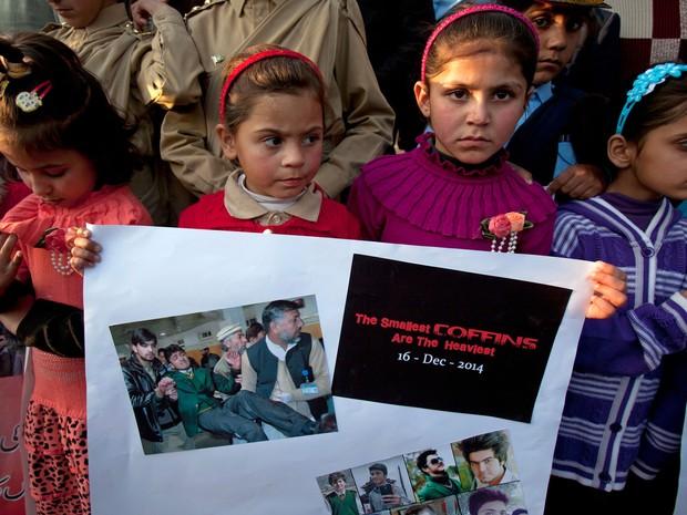 Crianças paquistanesas carregam cartazes com fotos das vítimas do atentado a escola onde morreram mais de 150 pessoas (Foto: Anjum Naveed/AP)