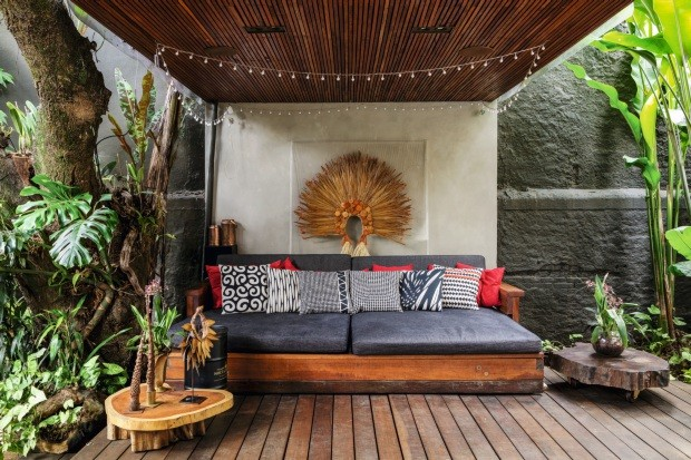 Área de descanso. Entre o corredor e o quintal, surge um lounge com sofá. À esq., na árvore pré-existente, costelas-de-adão e singônios. Na parede, quadro com o cocar tapuia (Eckhout), da EcoArts (Foto: Edu Castello / Editora Globo)