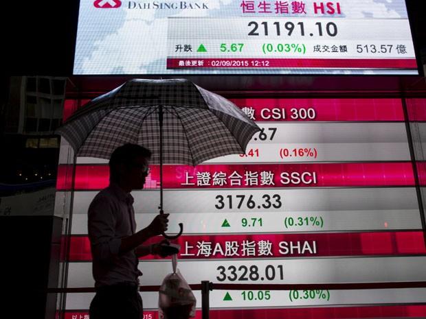 Homem passa em frente à painel de ações na China  (Foto: Reuters)