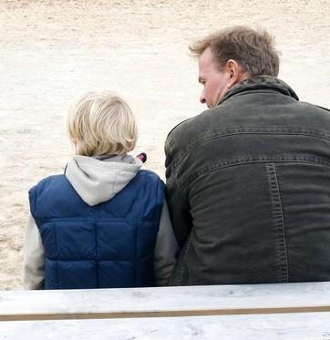 Homem de costas com criança sentada ao lado (Foto: Shutterstock)