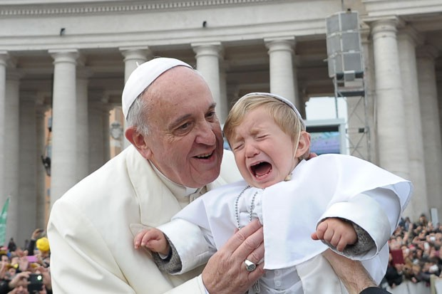 Criança chora ao ser entregue ao Papa Francisco nesta quarta-feira (26) no Vaticano (Foto: L'Osservatore Romano/AP)